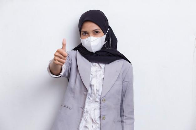 흰색으로 포즈를 취한 코로나 바이러스 covid19를 보호하기 위해 의료용 얼굴 마스크를 쓴 아시아 이슬람 여성