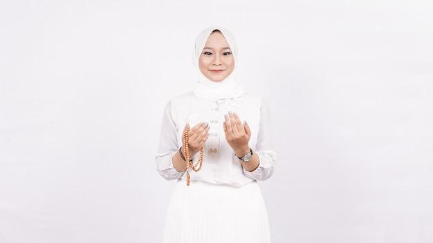 Азиатская мусульманка с четками молится в белом пространстве