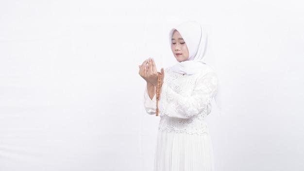 Азиатская мусульманка с четками молится в белом