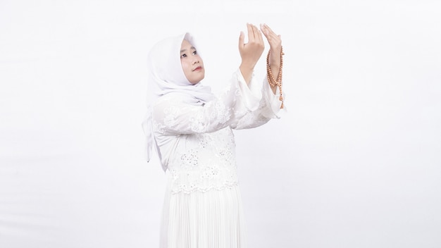 Asian muslim woman wearing prayer beads pray in white