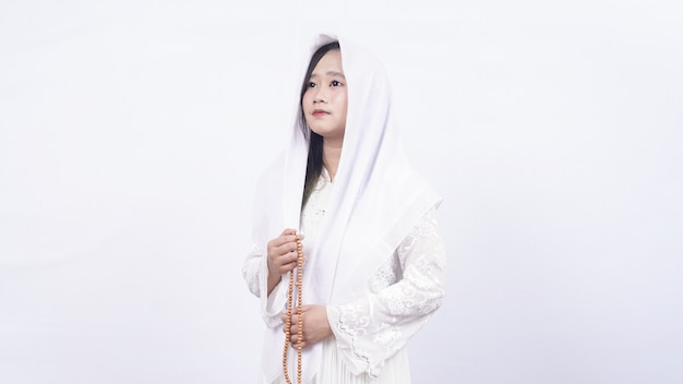 Asian muslim woman wearing prayer beads pray with tasbih in white