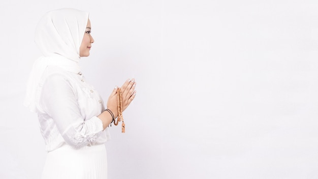 Asian muslim woman wearing prayer beads welcoming guests or ied fitr greeting in white space