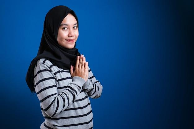 青い背景にゲストのジェスチャーを歓迎するアジアのイスラム教徒の女性