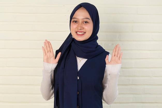 ゲストのジェスチャーを歓迎するアジアのイスラム教徒の女性