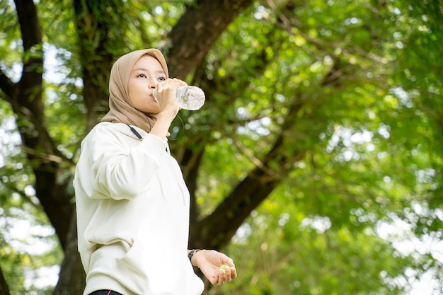 Asian muslim woman with head scarf drinking a bottle of water during exercising outdoor