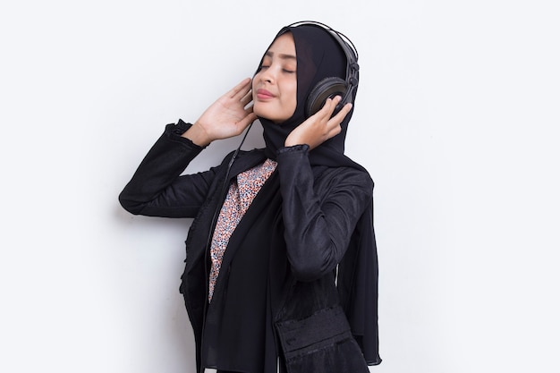 Asian muslim woman with hijab listening to music on headphones isolated on white background