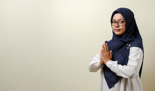 イードムバラクまたはイードフィトルまたはイードアルフィトルのためにゲストを歓迎するために身振りで示すアジアのイスラム教徒の女性