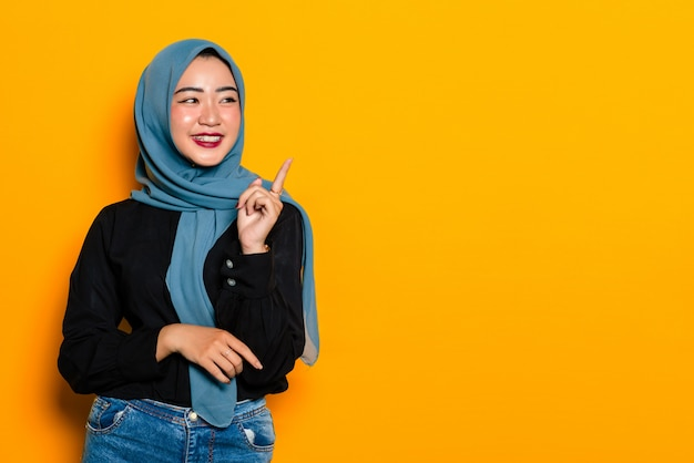 Asian muslim women pointing to empty space