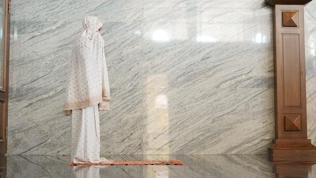モスクで祈るアジアのイスラム教徒の女性