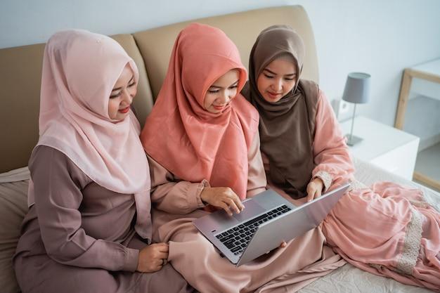 Азиатки-мусульманки, использующие ноутбук для поиска предметов в интернет-магазине, когда остаются дома