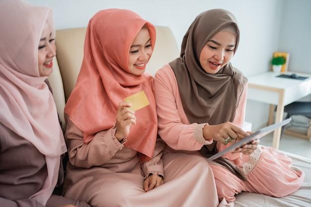 Азиатские мусульманки используют планшет для поиска предметов в интернет-магазине
