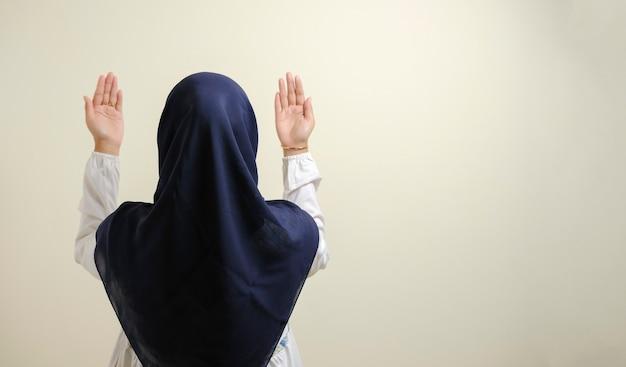 히잡을 쓰고 옆에 빈 공간을 두고 기도하는 아시아 이슬람 여성