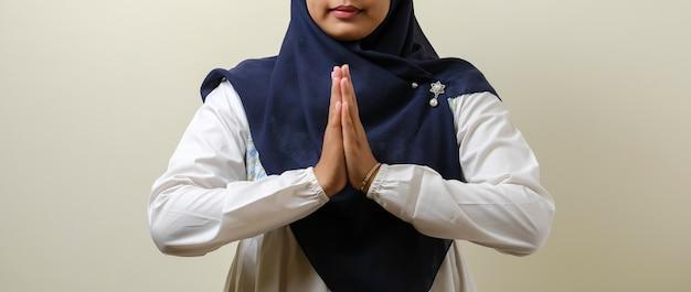 イードムバラクまたはイードフィトルまたはイードアルフィトルのためにゲストを歓迎するために身振りで示すカメラに笑みを浮かべてヒジャーブを身に着けているアジアのイスラム教徒の女性 Premium写真