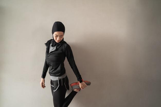 脚のストレッチを行うヒジャーブスポーツウェアを着ているアジアのイスラム教徒の女性