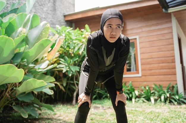 ヒジャーブスポーツウェアを身に着けているアジアのイスラム教徒の女性は汗をかくし、疲れています
