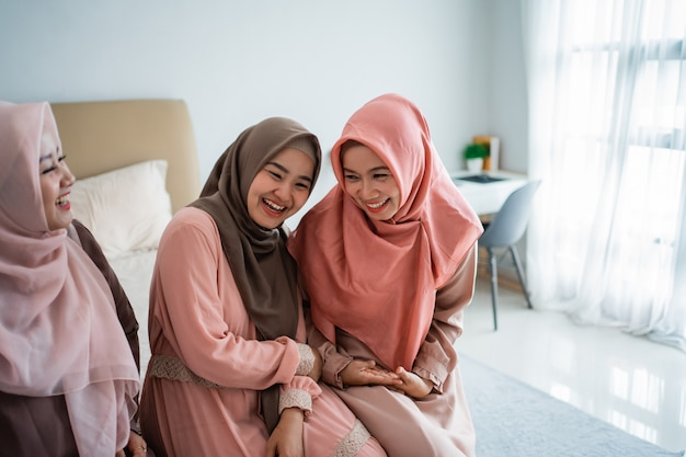 Asian muslimah woman enjoy chatting while sitting on the bed
