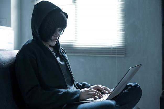 Азиатские ботаник очки женщина с капюшоном, сидя на диване, с помощью ноутбука в комнате в общежитии