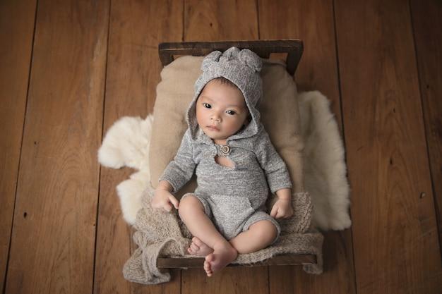 Азиатский новорожденный ребенок носит рубашку с капюшоном на кровати