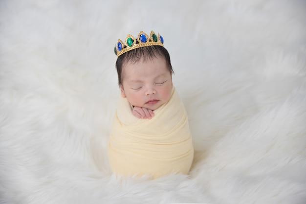Азиатский новорожденный ребенок в короне в желтом пелене спит на белом пушистом коврике
