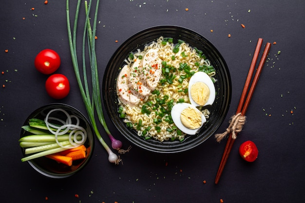 Asian noodle soup. ramen with chicken, vegetables and egg in black bowl. top view.