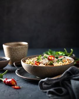 아시아 국수 스프, 어두운 배경에 세라믹 그릇에 두부와 야채라면, 선택적