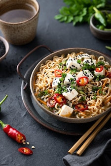 Asian noodle soup, ramen with tofu and vegetables in ceramic bowl on dark background, selective
