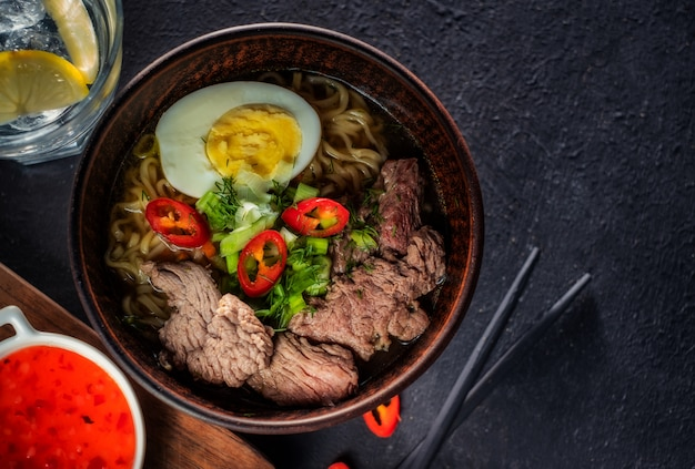 Asian noodle soup with beef, egg, red pepper and herbs on a dark table, top view