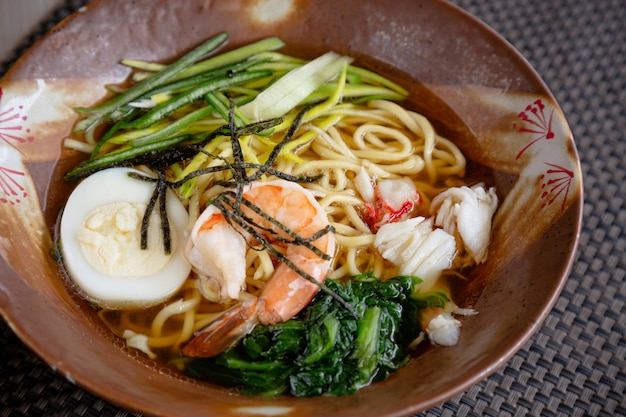 Asian noodle soup with crab meat, boiled egg, shrimp and spinach