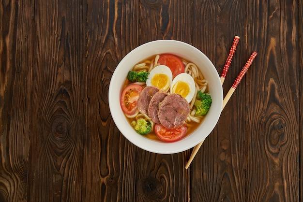 Азиатский суп с лапшой с овощами, яйцом, говядиной и палочками для еды на деревянном фоне и копией пространства, вид сверху
