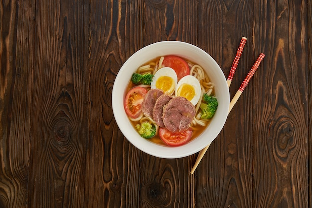 Asian noodle soup with vegetables, egg, beef and chopsticks on wooden background and copy space, top view