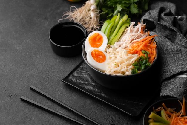 Tagliatelle asiatiche in una ciotola con uova e verdure