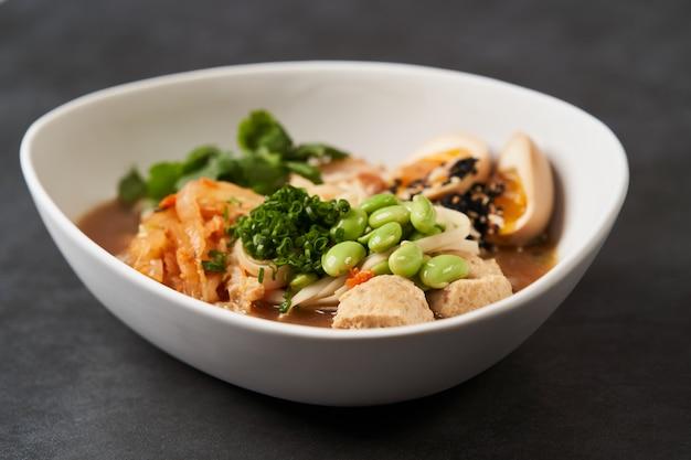 Азиатский суп с лапшой, рамэн с курицей, тофу, овощами и яйцом, крупным планом