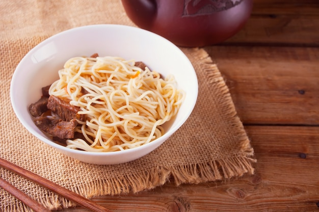 Asian noodles with beef, vegetables in bowl with chopsticks, rustic wooden. asian style dinner. chinese japanese noodles