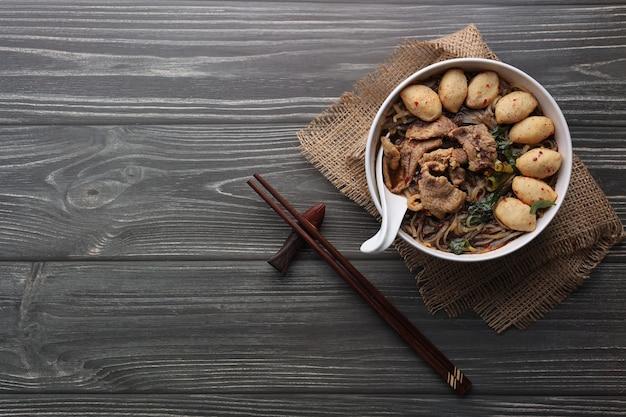 Азиатская лапша со свининой, свиными шариками, палочками для еды и овощами на темном фоне