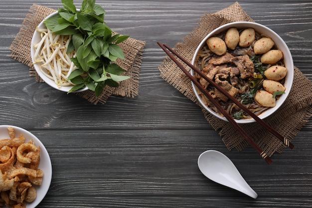 Азиатская лапша со свининой, свиными шариками, свиными шкварками и овощами на темном фоне