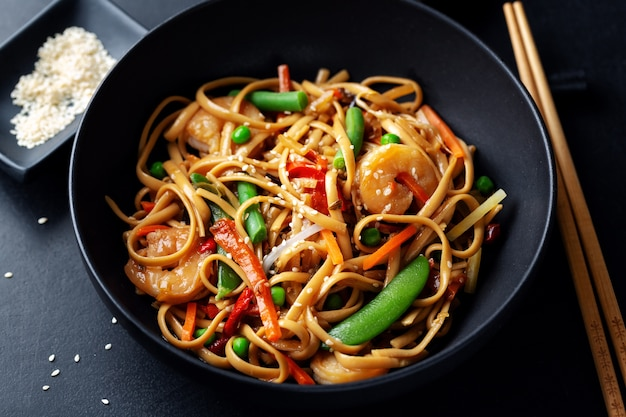 Asian noodles with prawns and vegetables served in bowl on dark background.