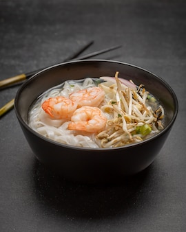 Asian noodles with shrimps and seafood in black bowl