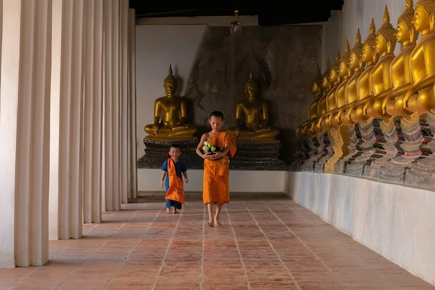 Asian novice monk walking in temple phutthaisawan at ayutthaya, thailand.