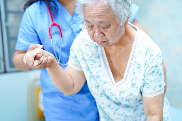 Asian nurse physiotherapist care, help and support senior or elderly woman patient.