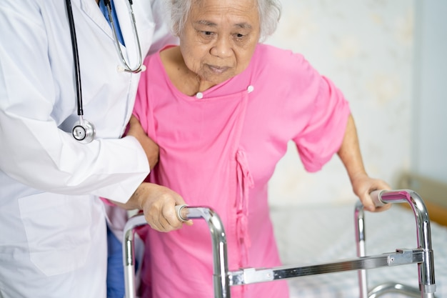 아시아 간호사 물리 치료사 의사 치료, 도움 및 병원 병동에서 워커, 건강 한 강력한 의료 개념 수석 또는 노인 할머니 여자 환자 도보를 지원합니다.