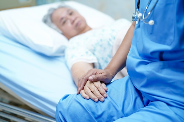 Asian nurse physiotherapist doctor care, help and support elderly old lady woman patient.