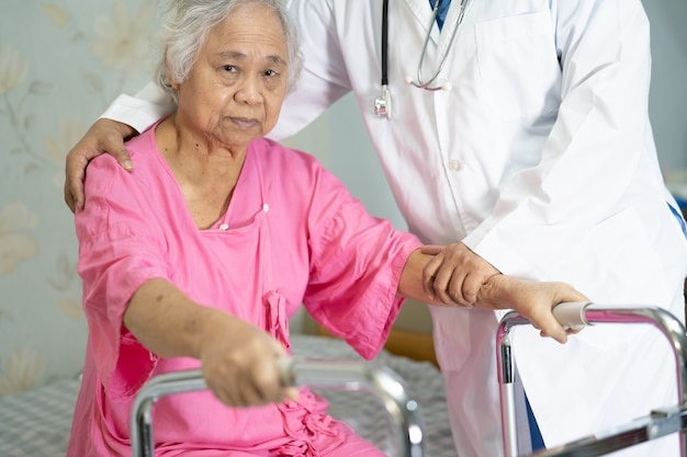 Asian nurse physiotherapist doctor care, help and support senior or elderly old lady woman patient walk with walker at hospital ward, healthy strong medical concept.
