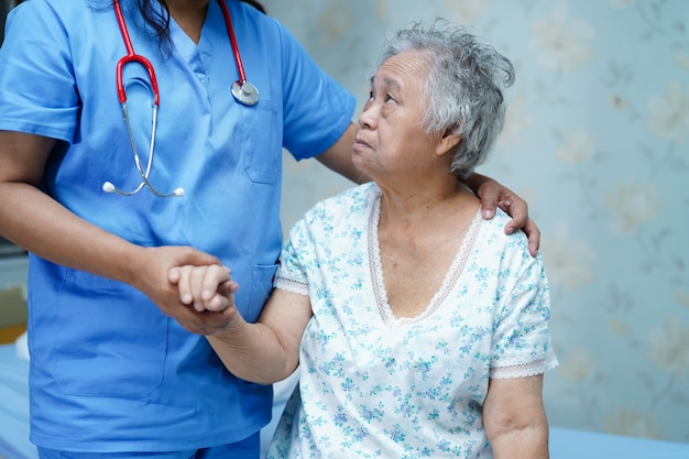 Asian nurse physiotherapist doctor care, help and support senior woman patient in hospital.