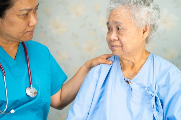 Asian nurse physiotherapist doctor touching asian senior or elderly old lady woman patient with love, care, helping, encourage and empathy at nursing hospital ward, healthy strong medical concept.
