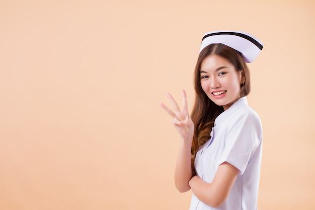 3本の指を上向きにするアジアの看護師