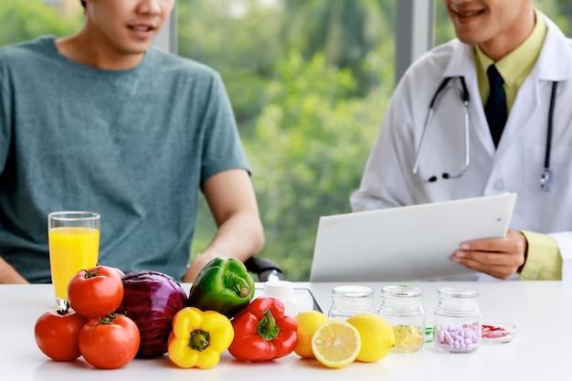 Азиатский врач диетолог носить стетоскоп, держа документы и объясняя это пациенту. фрукты, соки и питание на столе.