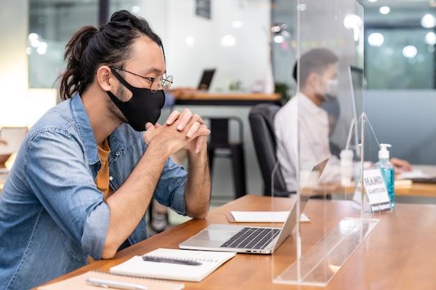 Азиатский офисный работник бизнесмен в защитной маске работает в новом нормальном офисе