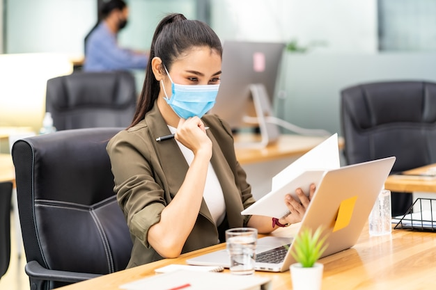 Азиатский офисный служащий-бизнесвумен в защитной маске работает в новом нормальном офисе