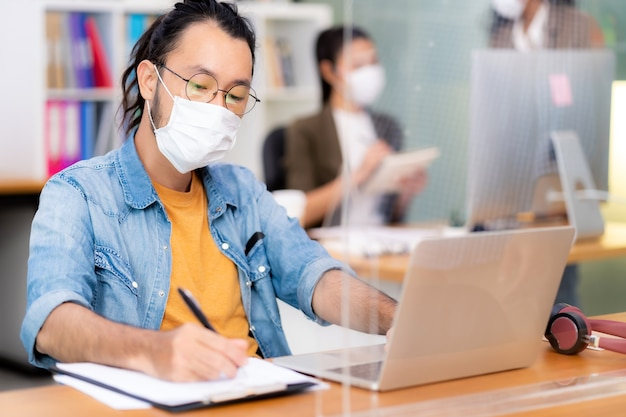 アジアのオフィスの従業員は、新しい通常のオフィスで防護マスクを着用します。社会的距離の練習はコロナウイルスcovid-19を防ぎます。