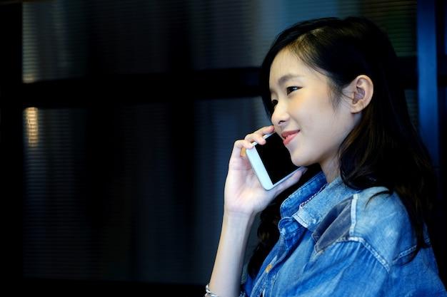 携帯電話で話しながら笑っているアジアのオフィスの女の子